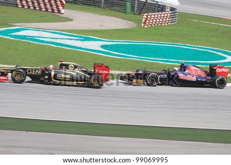 SEPANG, MALAYSIA - MARCH 23: Daniel Ricciardo of Toro Rosso and Kimi Raikkonen of Lotus in action during Friday practice at Petronas Formula 1 Grand Prix on March 23, 2012 in Sepang, Malaysia - stock photo