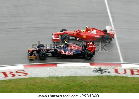 SEPANG, MALAYSIA - MARCH 25 : Felipe Massa of Ferrari and Jean-Eric Vergne of Toro Rosso side by side during race day of Petronas F1 Malaysian Grand Prix on March 25, 2012 in Sepang, Malaysia - stock photo