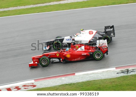 SEPANG, MALAYSIA-MARCH 25 : Fernando Alonso of Ferrari race side by side with Sergio Perez of Sauber-Ferrari during race day of F1 Petronas Malaysian Grand Prix on March 25, 2012 in Sepang, Malaysia - stock photo