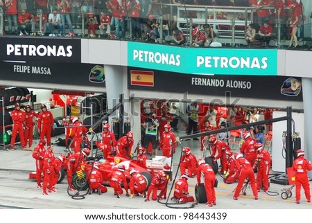SEPANG, MALAYSIA - MARCH 25: Ferrari F1 Team crews does pit-stop practice at the 2012 F1 Petronas Malaysian Grand Prix at Sepang International Circuit on March 25, 2012 in Sepang, Malaysia
