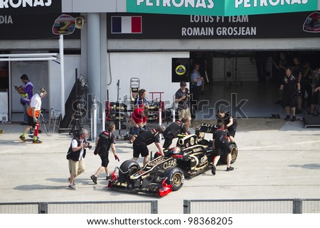 SEPANG, MALAYSIA - MARCH 23: French Romain Grosjean of Team Lotus pushed back to his pit garage during Friday practice at Petronas Formula 1 Grand Prix March 23, 2012 in Sepang, Malaysia - stock photo