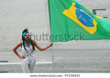 SEPANG, MALAYSIA - MARCH 25 : Grid girl holds Brazil flag during the opening ceremony of F1 Petronas Malaysian Grand Prix at Sepang F1 circuit on March 25, 2012 in Sepang, Malaysia - stock photo