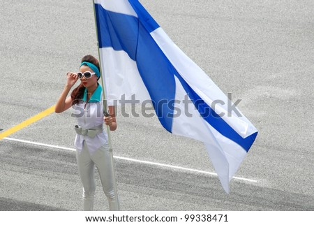 SEPANG, MALAYSIA - MARCH 25 : Grid girl holds Finland flag during the opening ceremony of F1 Petronas Malaysian Grand Prix at Sepang F1 circuit on March 25, 2012 in Sepang, Malaysia - stock photo