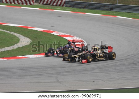 SEPANG, MALAYSIA - MARCH 23: Kimi Raikkonen of Lotus and Daniel Ricciardo of Toro Rosso in action during Friday practice at Petronas Formula 1 Grand Prix on March 23, 2012 in Sepang, Malaysia - stock photo
