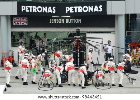 SEPANG, MALAYSIA - MARCH 25: McLaren Mercedes Team crews does pit-stop practice at the 2012 F1 Petronas Malaysian Grand Prix at Sepang International Circuit on March 25, 2012 in Sepang, Malaysia - stock photo