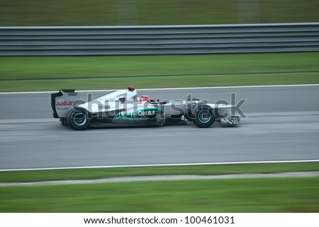 SEPANG, MALAYSIA - MARCH 25 : Panning shot of Mercedes Team driver Michael Schumacher during the race day of F1 Petronas Malaysian Grand Prix at Sepang F1 circuit on March 25, 2012 in Sepang, Malaysia - stock photo