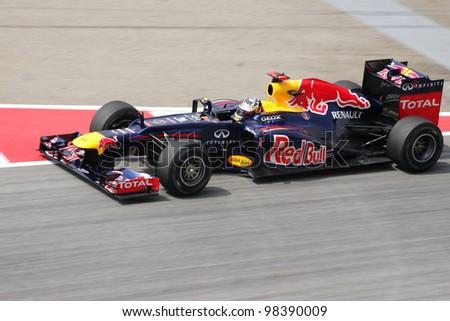 SEPANG, MALAYSIA - MARCH 23 : Red Bull Racing driver Sebastian Vettel of Germany drives during Petronas Malaysian Grand Prix  practice session at Sepang F1 circuit 23 March, 2012 in Sepang,Malaysia. - stock photo
