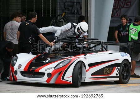 SEPANG, MALAYSIA - MAY 10, 2014: Driver CM Wong jumps into his race car during the pit-stop at the free practice session of the Malaysian Super Series Round 2 in Sepang International Circuit. - stock photo