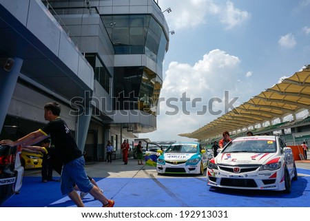 SEPANG, MALAYSIA - MAY 11, 2014: Marshals push the cars in for weighing after the Touring Car Series Asia race, as part of the Malaysian Super Series Rd 2 held at the Sepang International Circuit. - stock photo