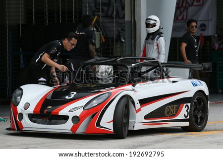 SEPANG, MALAYSIA - MAY 10, 2014: The race car of CM Wong undergoes check during the pit-stop at the free practice session of the Malaysian Super Series Round 2 in Sepang International Circuit. - stock photo
