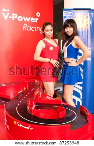 SEPANG, MALAYSIA - OCT 21: A pair of unidentified Malaysian models posed during the promotion of Shell V-Power Product at the Malaysian Motorcycle Grand Prix 2011 on October 21, 2011 in Sepang, Malaysia.