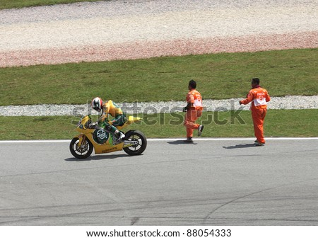 SEPANG, MALAYSIA - OCT. 21: Alex De Angelis of JIR Moto2 gets help after crash during practice session of Shell Advance Malaysian Moto GrandPrix on Oct. 21 2011 in Sepang, Malaysia. - stock photo