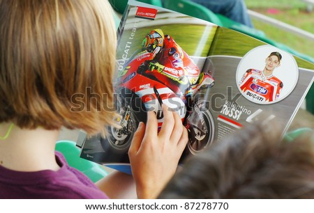 SEPANG, MALAYSIA-OCT 21: Unidentified fan reads the magazine MotoGP with Valentino Rossi pictures from Ducati Team on October 21, 2011 in Sepang, Malaysia. The Malaysian Grand Prix will take place on Oct 23., 2011 - stock photo