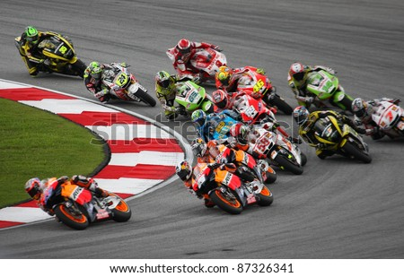 SEPANG, MALAYSIA - OCTOBER 23: MotoGP riders take turn 1 on race day of the Malaysian Motorcycle GP 2011 on October 23, 2011 at Sepang, Malaysia. Marco Simoncelli (58) died in a horrific crash later. - stock photo