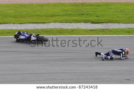 SEPANG, MALAYSIA - OCTOBER 21: Yamaha rider Katsuyuki Nakasuga  falls at turn 15 during free practice at the Shell Advance Malaysian Motorcycle GP 2011 on October 21, 2011 at Sepang, Malaysia. - stock photo