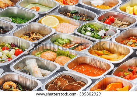 Separate portions of different food into containers - stock photo