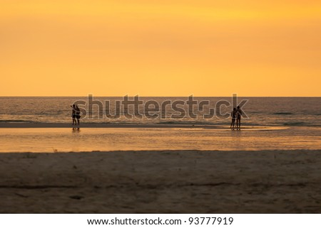 Separate two couple peoples on the beach at sunset - stock photo