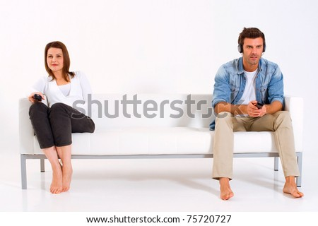 separated couple on the couch watching TV - stock photo