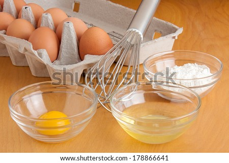 Separated cracked eggs in glass bowls, flour in a glass bowl, a silver whisk, and carton of eggs all on a cutting board. - stock photo