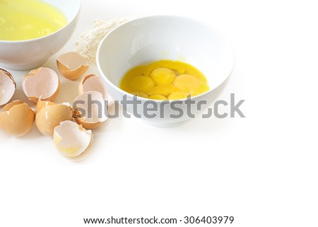 Separated eggs for baking, egg yolk and egg white in bowls, eggshells and some flour isolated on a white background with copy space - stock photo
