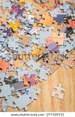 Separated jigsaw puzzle piece by pile of assorted puzzles. Shallow depth of field - stock photo