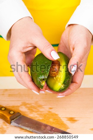 separates avocado into two parts on a wooden board