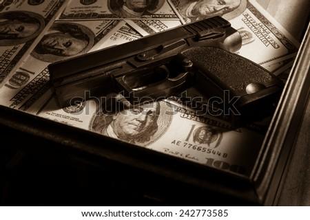 Sepia filtered of gun on dollar bills in briefcase.  - stock photo