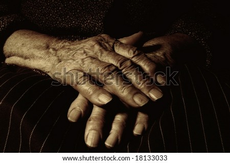 Sepia image of crossed hands of an old woman
