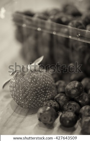 Sepia image of fresh blueberries and one strawberry from a farmer's market are on the counter ready for consumption. - stock photo