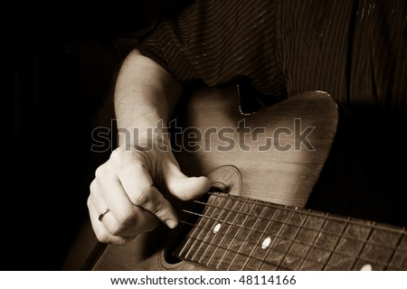 sepia image of man holding guitar - stock photo