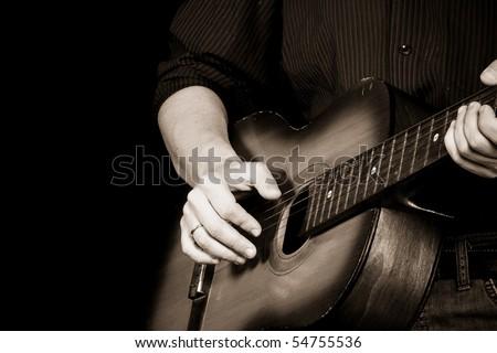 sepia image of man playing guitar - stock photo