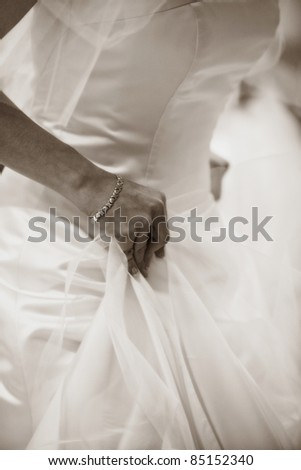 Sepia Picture of a Bride trying on her Gown - stock photo