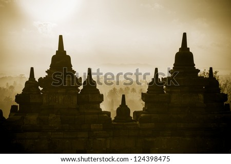 Sepia small stupas on the wall top level of  Borobudur, or Barabudur, temple Jogjakarta, Java, Indonesia at sunrise. It is a 9th-century Mahayana temple and the biggest  Buddhist Temple in Indonesia. - stock photo