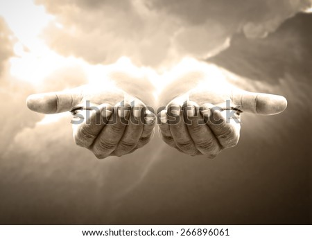Sepia tone. Human open empty hand with palms up over amazing sky background. - stock photo