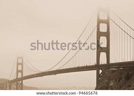 Sepia tone image of Golden Gate Bridge shrouded in fog in San Francisco - stock photo