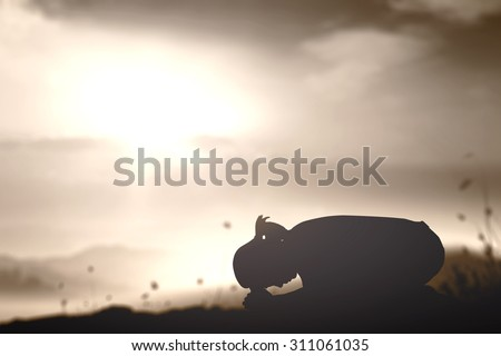 Sepia tone. Silhouette of woman kneeling and praying over beautiful sunset background. Christmas, International Day for the Abolition of Slavery, Forgiveness, Redeemer, Thanksgiving, Love concept. - stock photo