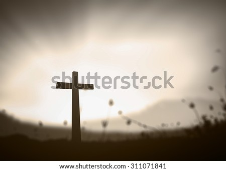 Sepia tone. Silhouette the cross over amazing light on blurred sunset background. - stock photo