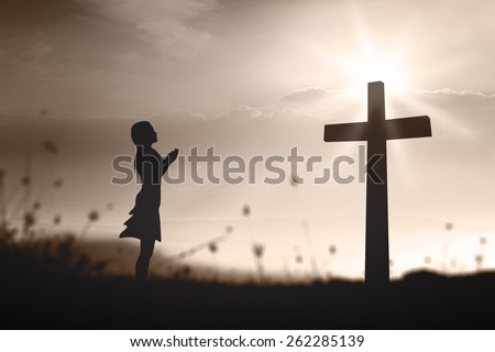 Sepia tone. Silhouette woman praying over the cross on beautiful sunset with amazing light background. - stock photo