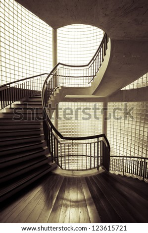 Sepia tone spiral staircase surrounded by mirror - stock photo