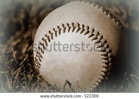 sepia-toned baseball in the grass - stock photo