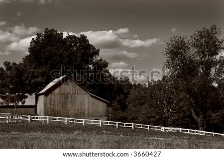 Sepia toned black and white photo of a barn and white fence in Harford County, Maryland - stock photo