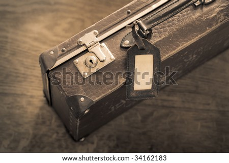 Sepia toned color photo of an old worn suitcase - stock photo