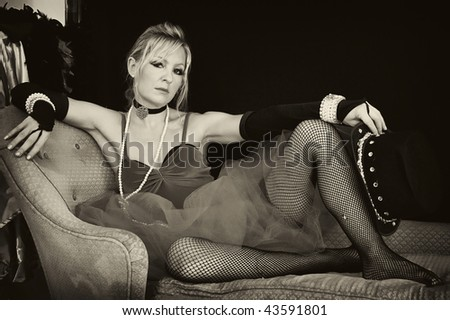 sepia toned full length image of blonde woman in sexy outfit holding hat. - stock photo