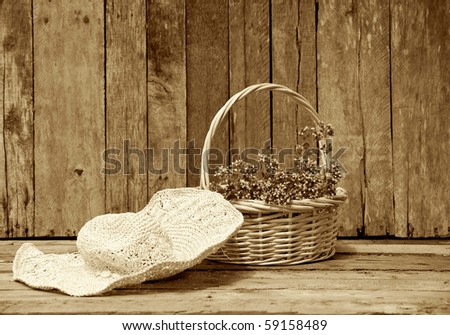 Sepia toned image of a basket of freshly cut oregano and a gardener's straw hat on a rustic barn wood background. - stock photo