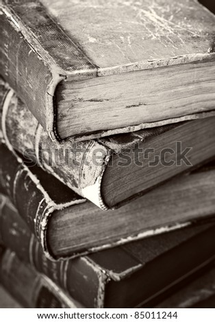 Sepia toned image of a stack of old worn books. - stock photo