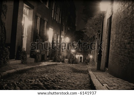 Sepia toned image of an old 19th Century cobble stone road in Boston Massachusetts, lit only by the gas lamps revealing the shuttered windows and brightly lit doorways of the rowhouses on Acorn Street - stock photo