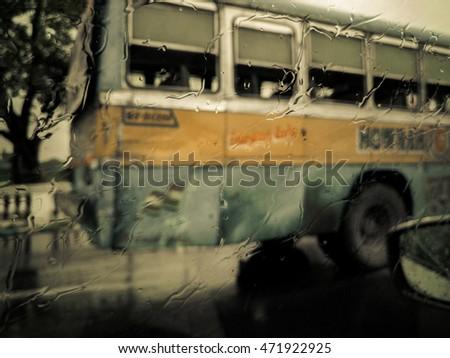Sepia toned image of focus on rain water droplets streaming across a car window with out of focus backdrop of a typical Kolkata public bus.