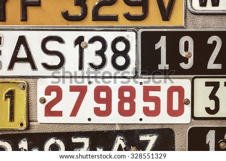 Sepia toned image of old number plates on a metal garage door - stock photo