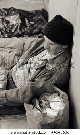 Sepia toned photo of a homeless man on the street, seated, surrounded by his meager belongings. - stock photo