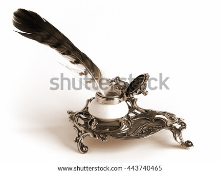 Sepia toned Photo shows Ornate antique brass inkwell with feather                                - stock photo